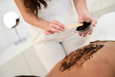 Woman cleans skin of the body with coffee scrub in spa wellness center