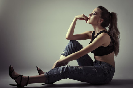 Young woman wearing black bra and blue jeans sitting on floor S