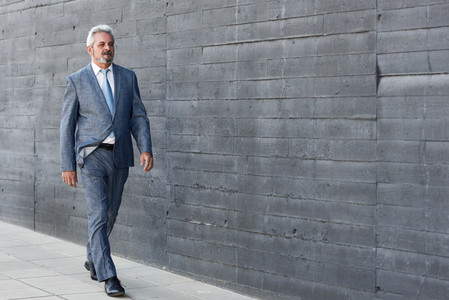 Serious senior businessman walking outside of modern office buil