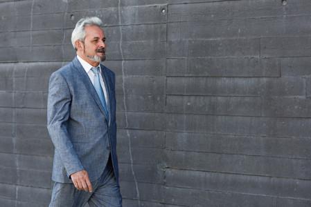 Serious senior businessman walking outside of modern office buil