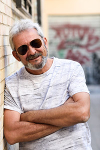 Mature man smiling with aviator sunglasses in urban background