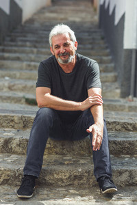 Mature man with white hair sitting on urban steps