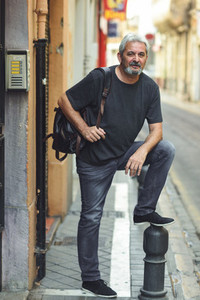 Mature tourist man with travel backpack in urban background