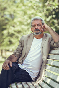 Pensive mature man sitting on bench in an urban park