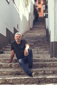 Mature man sitting on steps in urban background