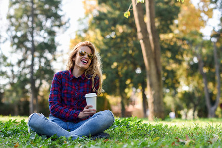 Beautiful woman drinking coffee in the park