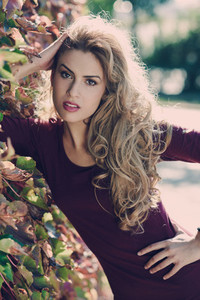 Young woman with long blond curly hair in urban background
