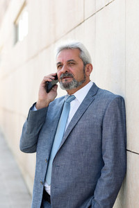 Senior businessman with smartphone outside of modern office buil