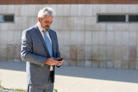 Senior businessman texting with smartphone outside of modern off