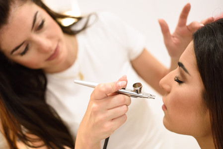 Make up artist using aerograph making an airbrush make up