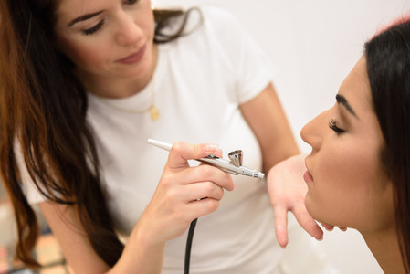 Make up artist using aerograph making an airbrush make up
