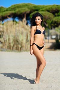 Young arabic woman with beautiful body in swimwear on a tropical beach