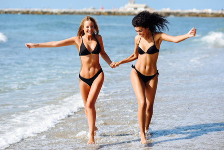 Two young women with beautiful bodies in swimwear on a tropical