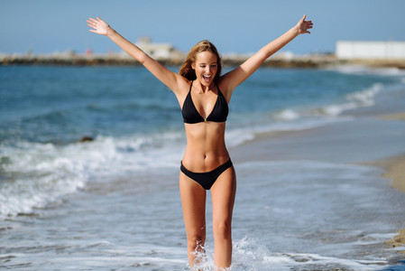 Young blonde woman with beautiful body in swimwear on a tropical beach with open arms