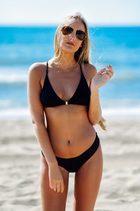 Blond woman in swimwear on the beach with aviator sunglasses