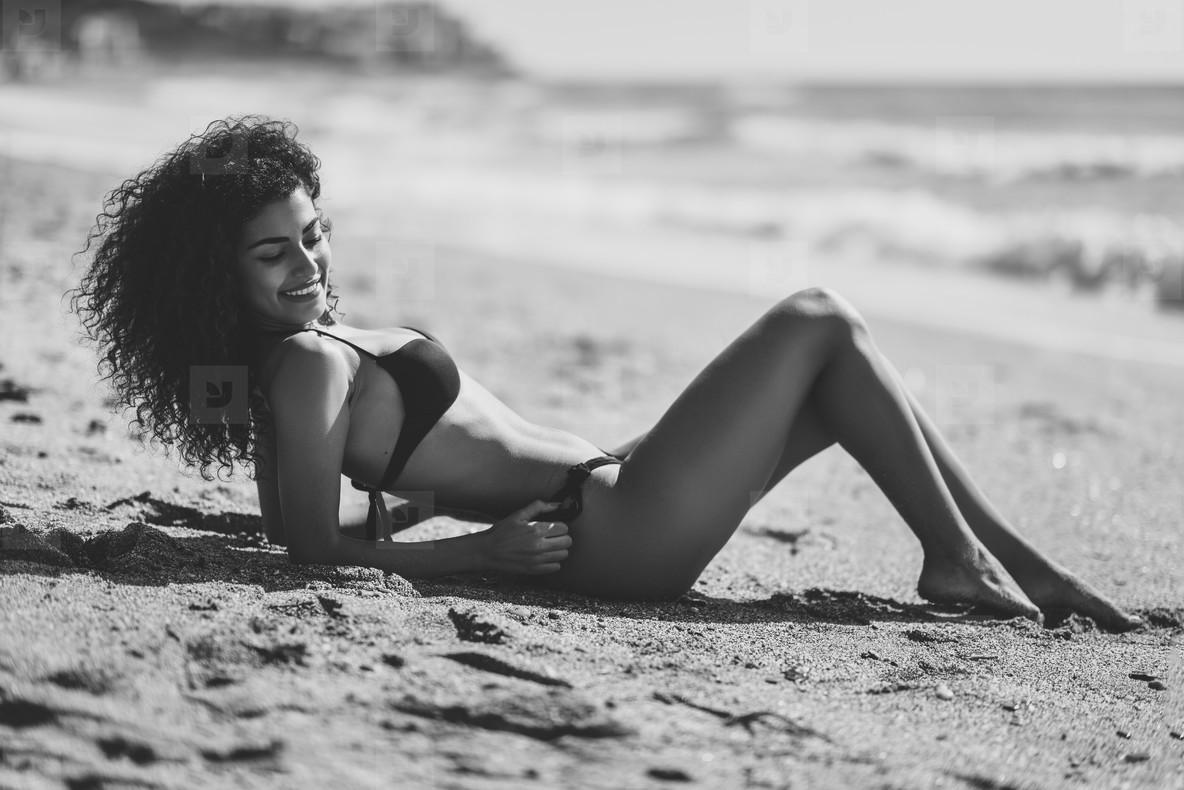 Arabic woman with beautiful body in bikini lying on the beach sa