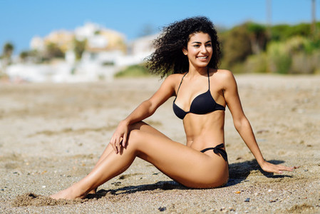 Arabic woman with beautiful body in bikini lying on the beach sand
