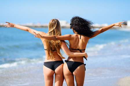 Rear view of two young women with beautiful bodies in bikini