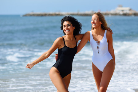 Two young women with beautiful bodies in swimsuit on a tropical