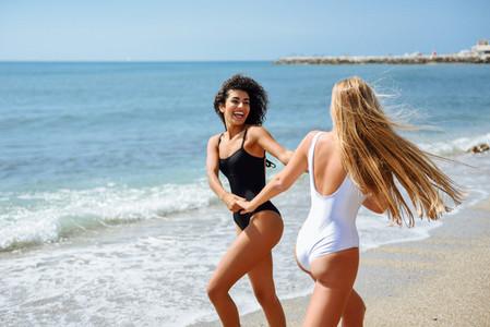 Two women in swimsuit having fun on the beach