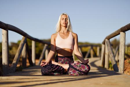 Caucasian female practicing yoga on wooden bridge