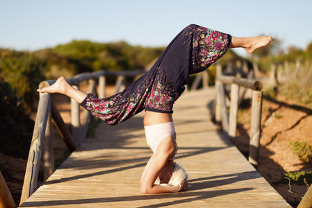 Caucasian female practicing yoga on wooden bridge