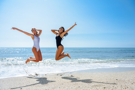 Two funny girls in swimsuit jumping on a tropical beach