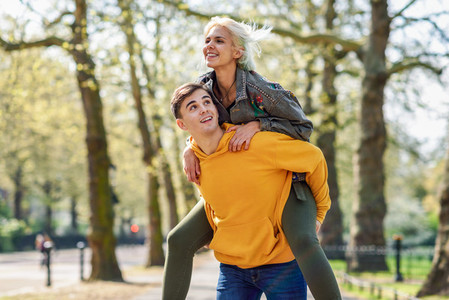 Funny couple in a urban park  Boyfriend carrying his girlfriend on piggyback