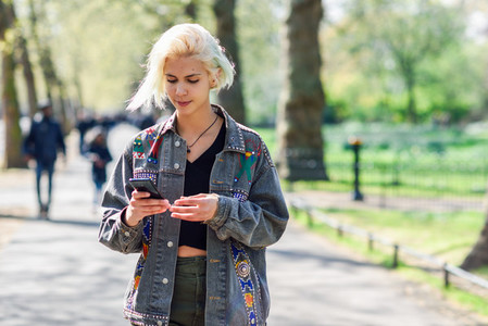 Young urban woman with modern hairstyle using smartphone walking in street in an urban park