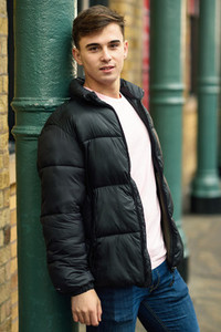 Young man standing in urban background with modern hairstyle