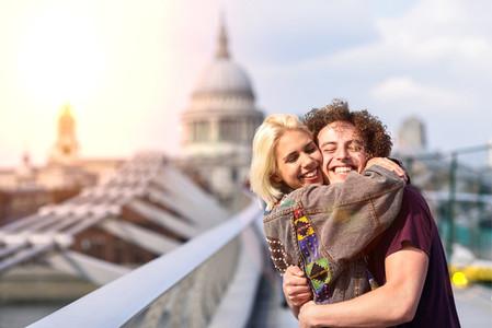 Happy couple hugging by Millennium bridge  River Thames  London