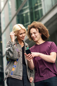 Happy couple using smartphone in urban background