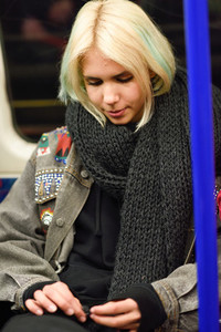 Young woman with short hair sitting inside underground wagon