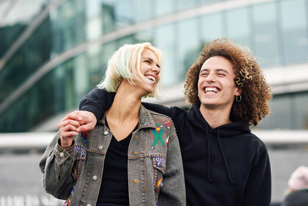 Happy young couple laughing in urban background