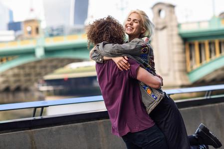Happy couple hugging near the Southwark bridge over River Thames  London