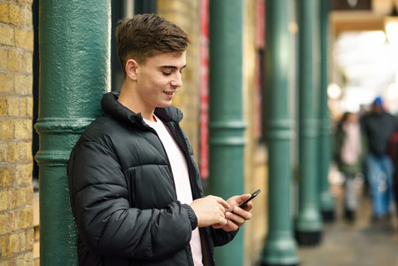 Young urban man using smartphone in urban background