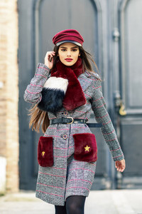Young beautiful girl with very long hair looking at camera wearing winter coat and cap outdoors