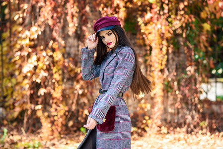 Young beautiful girl wearing winter coat and cap in autumn leaves background
