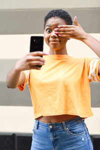 Funny black woman taking selfie photographs with happy expression outdoors