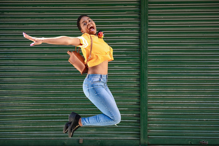 Young black woman jumping on blinds background