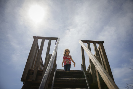 Little girl climbing to a wooden observation tower in a wetland
