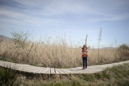 Little girl walking on a path of wooden boards in a wetland
