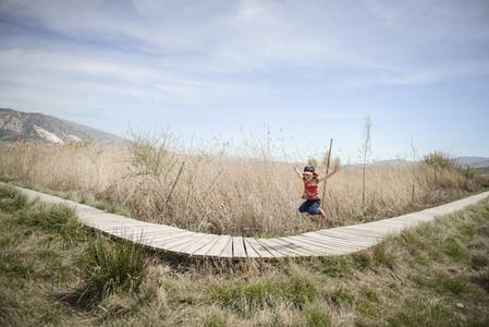 Little girl walking on a path of wooden boards in a wetland