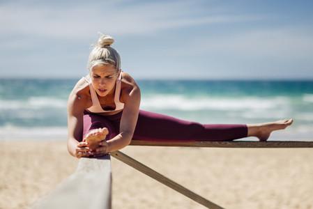 Caucasian blonde woman practicing yoga in the beach
