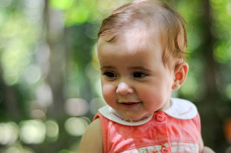 Six months old baby girl smiling outdoors