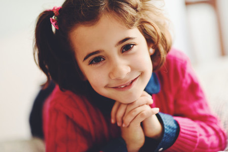 Adorable little girl with sweet smile lying down on bed