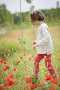 Cute little girl having fun in a poppy field