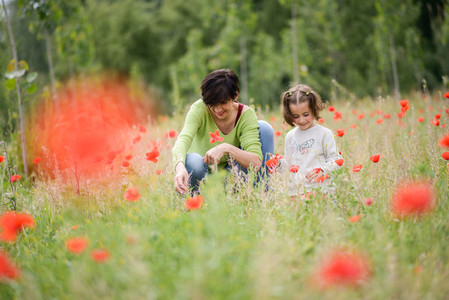 Mother with her little daughter in poppy field