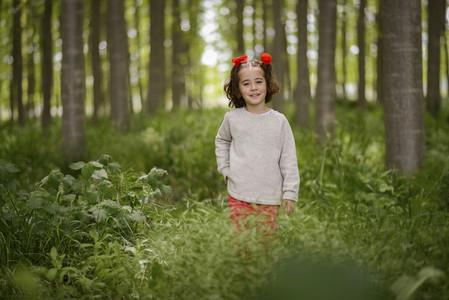 Cute little girl having fun in a poplar forest