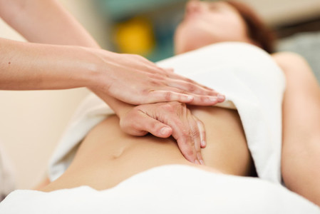 Therapist applying pressure on belly  Hands massaging woman abdomen